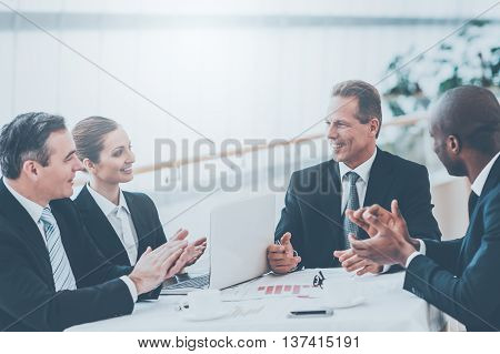 Good job! Business people in formalwear sitting together at the table and applauding