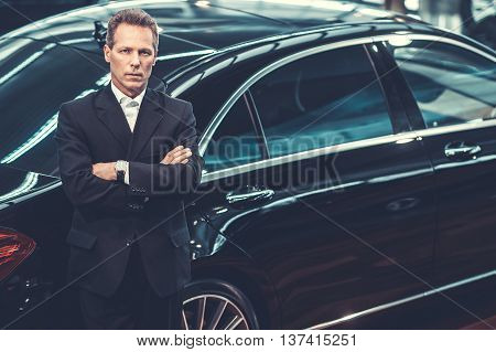 Choosing luxury. Top view of confident grey hair man in formalwear leaning at the car and looking at camera