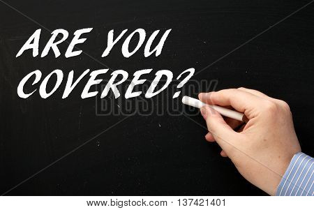 Hand writing the words Are You Covered in white text on a blackboard as a reminder to have insurance or a contingency plan in place