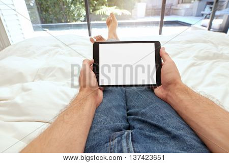 Man Using Touch Screen Computer On Bed