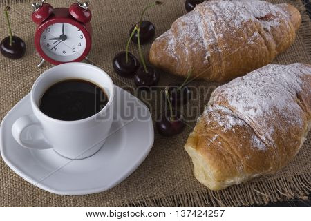 Alarm clock and breakfast with cherry, coffee and croissant on wooden background.