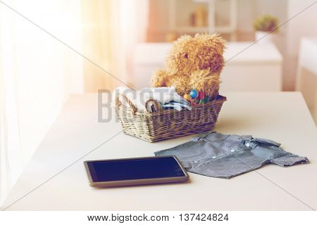 babyhood, motherhood, clothing, technology and object concept - close up of baby clothes and toys for newborn boy in basket with tablet pc computer at home
