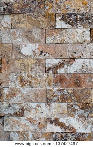 Background of a stone wall cladding texture brown stone bricks
