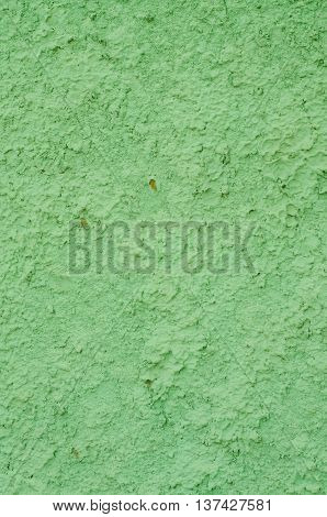 Background of a lime green stucco coated and painted exterior rough cast of cement and concrete wall texture decorative coating