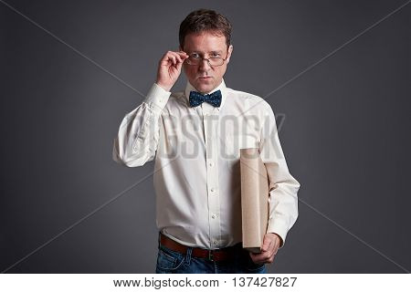 Portrait of a middle age man holding his glasses in a shirt and bowtie