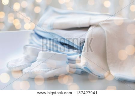 clothing, babyhood, motherhood and object concept - close up of white baby cardigan with bootees and pile of clothes for newborn boy with holidays lights