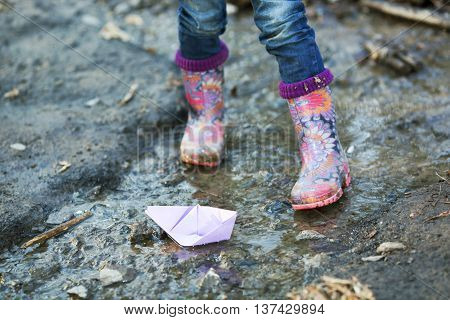 Beautiful colorful gumboots in a puddle with paper boats