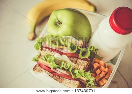 Lunch box with sandwich and fruits, copy space, toned