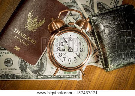 Thailand passport laying atop a pile of American dollars.Clock wallet.