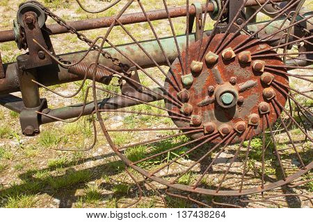 Old rusty Hay Turner.  Old agricultural equipment on hay.