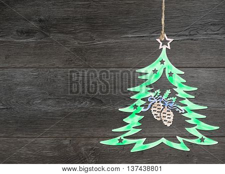 Homemade tree decoration. Christmas motif on background of dark brown wooden planks.