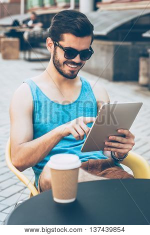 Surfing web from cafe. Handsome young man in casual wear holding digital tablet and looking at it with smile while sitting at sidewalk cafe outdoors