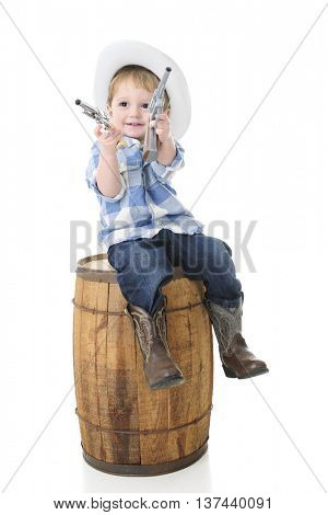 An adorable 2-year-old cowboy happily sitting on an old barrel with a toy gun in each hand.  On a white background.