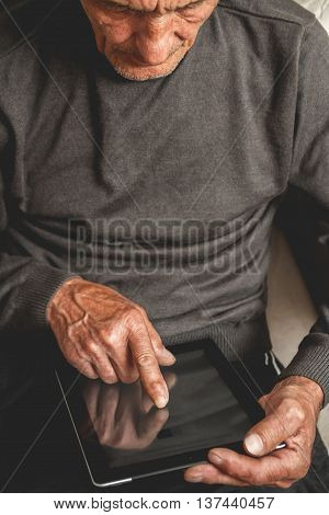 Senior sitting on the couch with a tablet in hands. Online education retirement concept. e-Learning. mock up