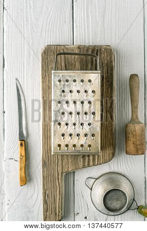 Grater plunger strainer and knife on the white wooden table vertical