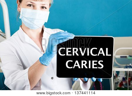 technology, internet and networking in medicine concept - femail dentist holding a tablet pc with cervical caries sign. at the dental equipment background.