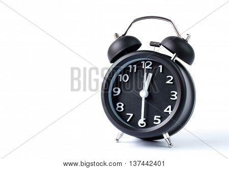 Black double bell alarm clock showing half past twelve on white background