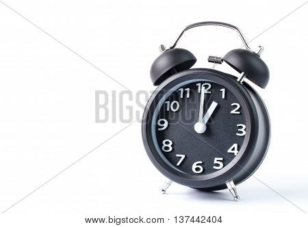 Black double bell alarm clock showing one o'clock on white background
