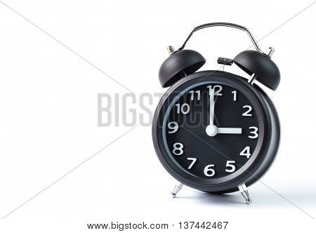 Black double bell alarm clock showing three o'clock on white background