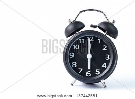 Black double bell alarm clock showing six o'clock on white background