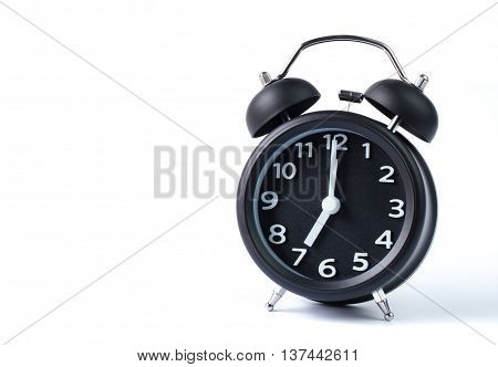 Black double bell alarm clock showing seven o'clock on white background
