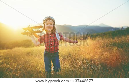 happy child dreams of traveling and playing with an airplane pilot aviator in outdoor in the summer
