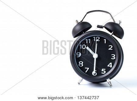 Black double bell alarm clock showing half past ten on white background
