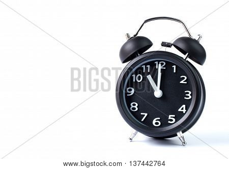 Black double bell alarm clock showing eleven o'clock on white background