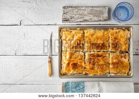 Greek pie spanakopita in the metal pan with table ware horizontal