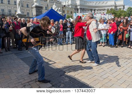 Kiev, Ukraine - May 21, 2016: Guitarist and dancing townspeople at St. Michael's Square during the celebration of Europe Day