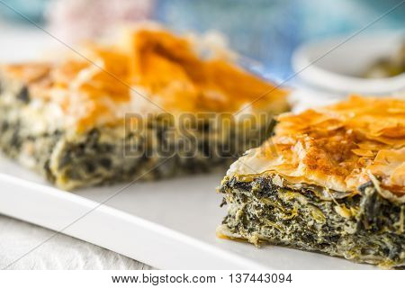 Greek pie spanakopita on the white plate with blurred accessorizes horizontal