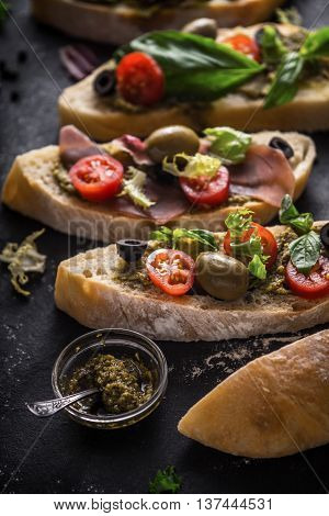 Slices of ciabatta with olives tomatoes and basil on the black stone table vertical