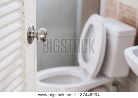 Close up, toilet door opening, with stationery ware, selective focus on door knob