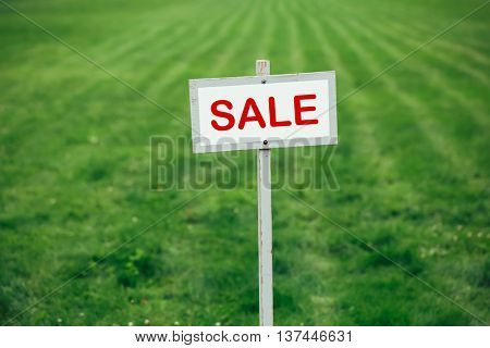 sale sign against trimmed lawn background