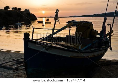 Fishing boats on a beach in front of ruins of a roman fortress at sunset, Sithonia, Greece