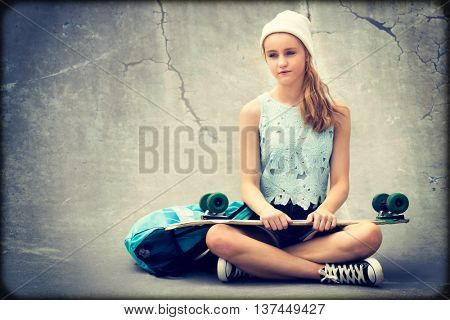 Teenage skater girl holding skateboard