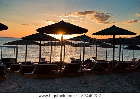 Straw parasols on a beach at sunset in Sithonia, Greece