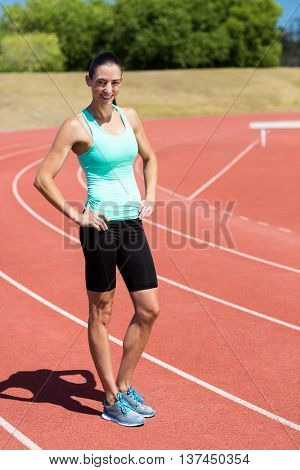 Portrait of female athlete standing on running track with hands on hips