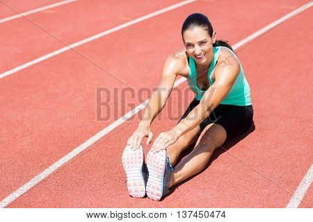 Portrait of female athlete doing stretching exercise on running track