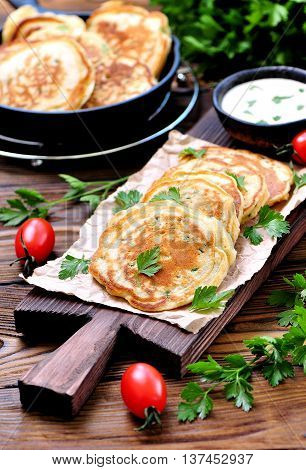 Pancake with parsley and spring onions on a wooden background