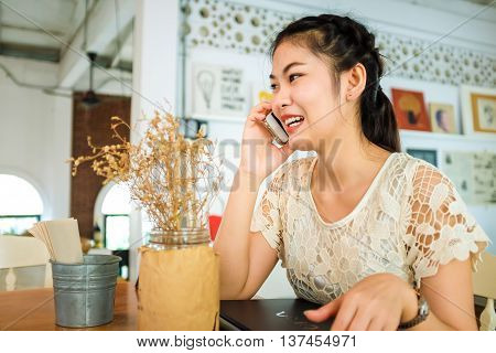 Asian Beautiful Girl Talking Her Mobile Phone In Cafe.