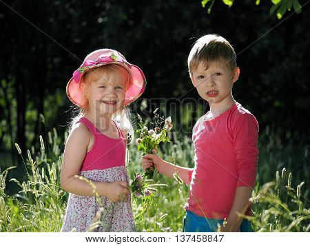 Boy gives a girl a bouquet. Young children with stunning views emotions. Girl in a hat. Summer sun wild flowers