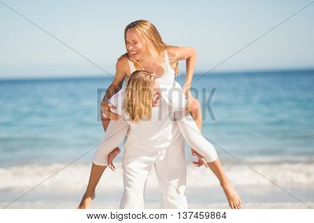 Young man giving piggy back ride to woman on beach