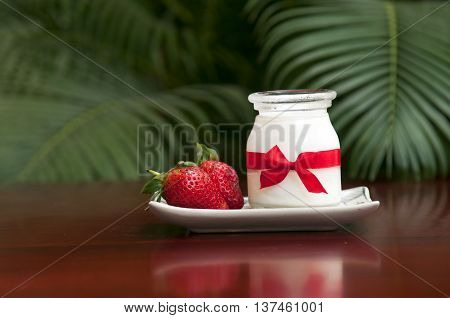 Yogurt with fresh strawberries on the table