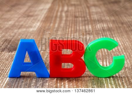 ABC spelling of colorful plastic letters on wooden background