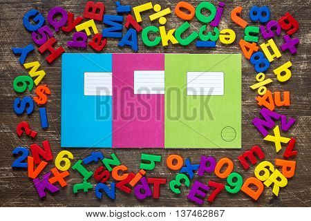 Three exercise books and border of colorful letters and numbers
