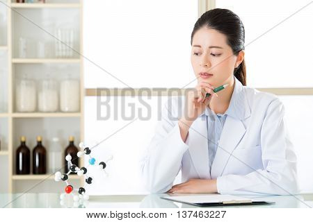 Asian Female Chemist Try To Figure Out Chemical Formula On Clipboard