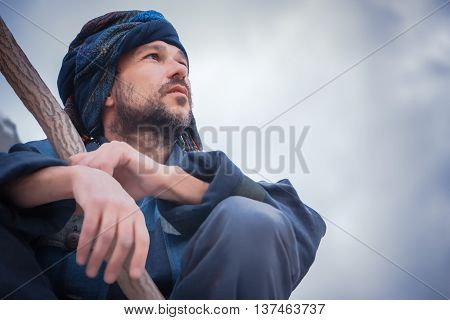 Man in the blue patterned turban with a stick sitting and seriously looking to the side on a light background. Selective focus on face.