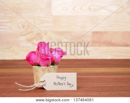 Pink rose flower in the basket and handwriting Happy Mother's Day on brown label paper with dark wood background