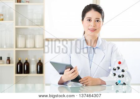 Asian Female Chemist Use Notepad To Research For Future Chemical Formula